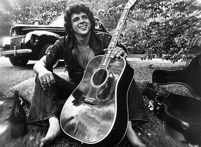1975: Songwriter and guitarist Bobby Whitlock poses for a portrait in front of an old car next to a bottle of Dom Perignon champagne holding an acoustic guitar in circa 1975. (Photo by Michael Ochs Archives/Getty Images)